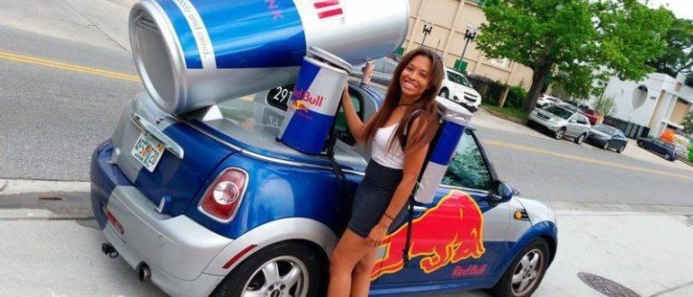 Девушка стоит рядом с брендированным автомобилем RedBull