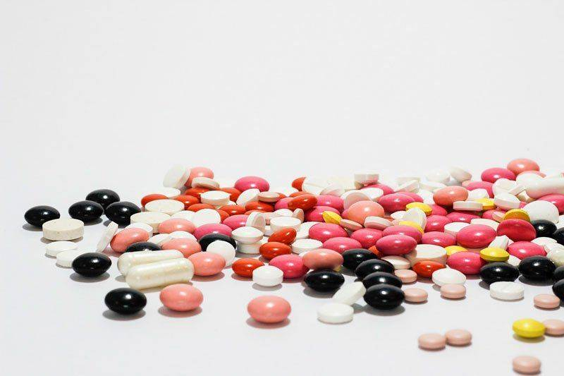 Рассыпанные по столу таблетки и капсулы