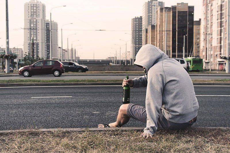 Мужчина выпивает на улице