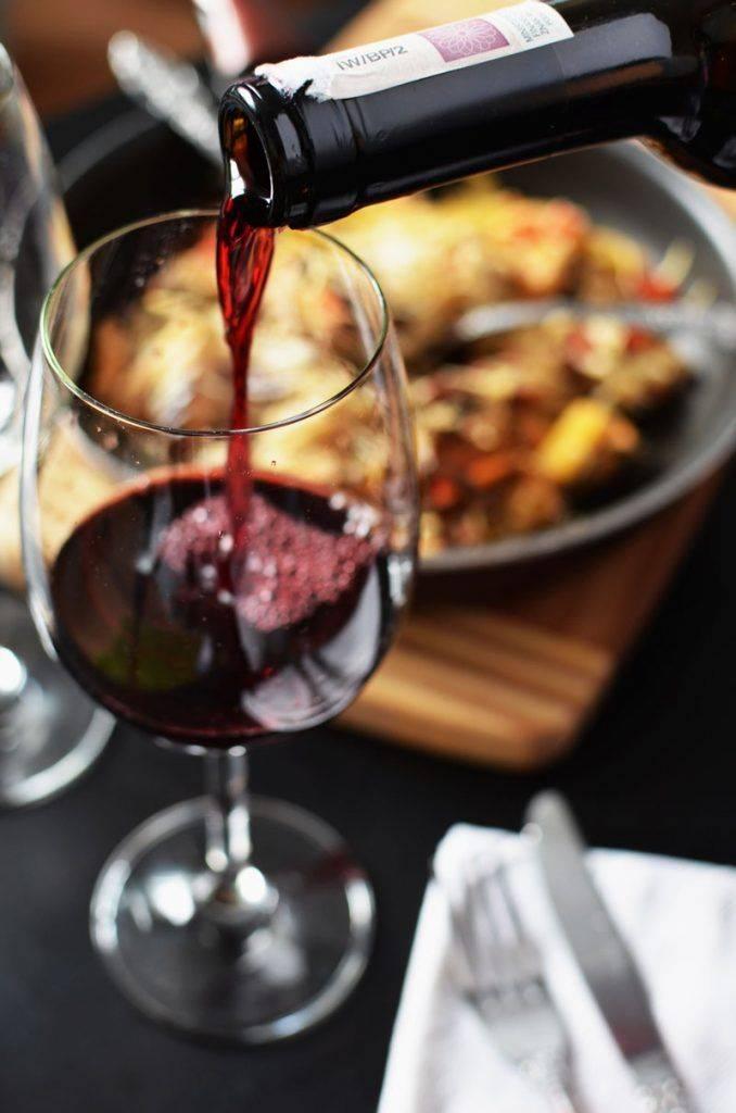 Красное вино наливается из бутылки в бокал