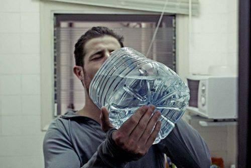 Мужчина пьет воду из канистры