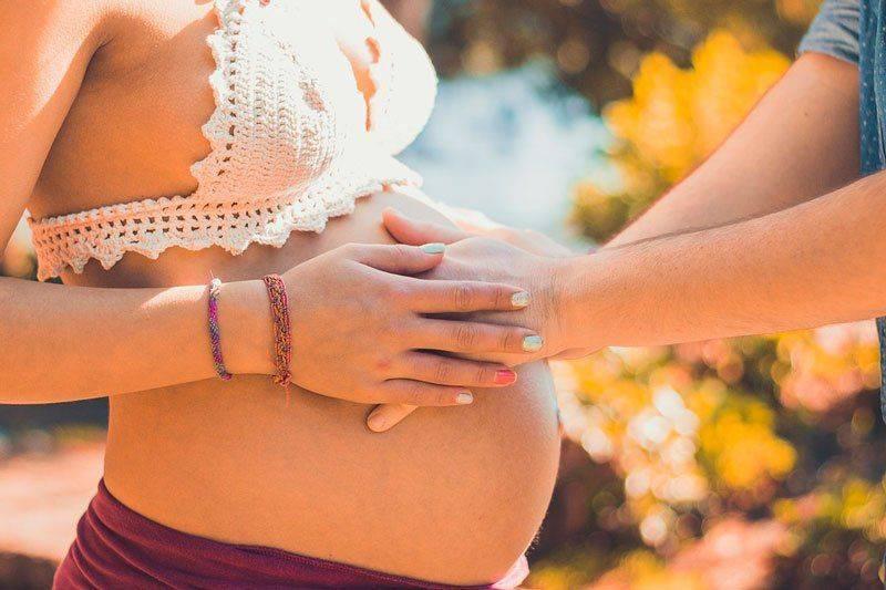 Мужчина кладет руки на живот беременной женщине