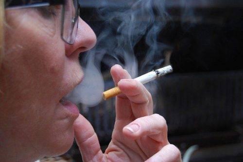 Женщина курит сигарету